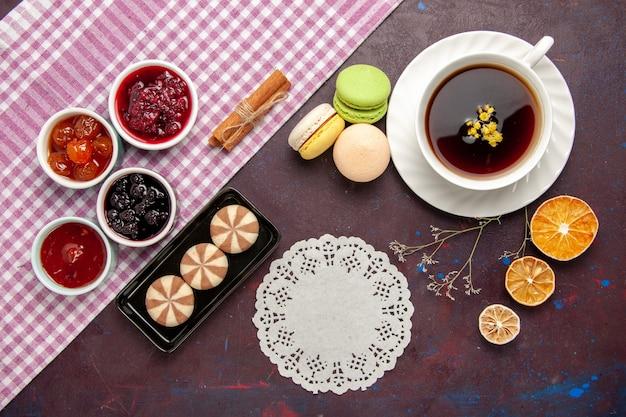 Vista superior de la taza de té dentro de la placa y la taza en la superficie oscura bebida de té dulce de fotografía en color
