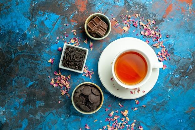 Vista superior de una taza de té diferentes chocolates en tazones pequeños en el espacio de copia de superficie azul rojo
