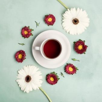 Vista superior taza de té de frutas y arreglo de margaritas