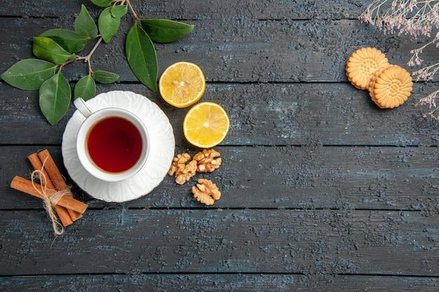 Vista superior de la taza de té con galletas en el azúcar de tarta de galletas dulces de mesa oscura