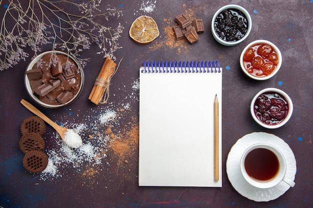 Vista superior de una taza de té con galletas y mermelada en el espacio oscuro