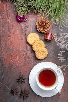 Vista superior de la taza de té con galletas en el té dulce de galletas de mesa oscura