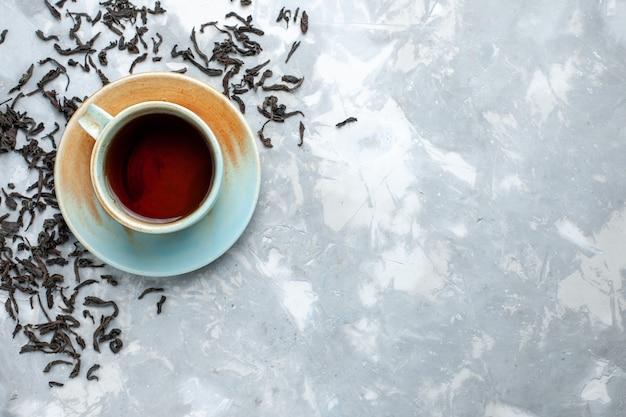 Vista superior de la taza de té con granos de té secos frescos en la mesa de luz, desayuno de bebida de té
