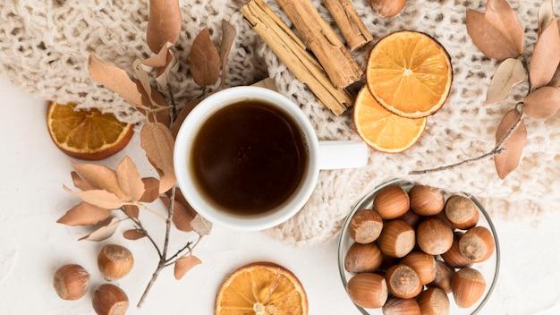 Vista superior de la taza de té con hojas de otoño y ramitas de canela