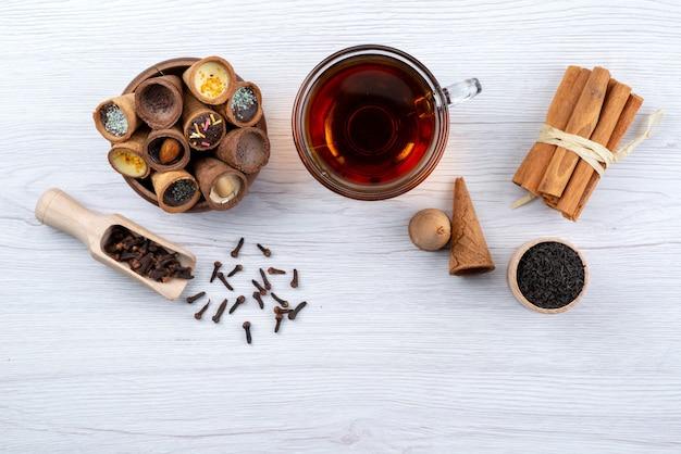 Vista superior de una taza de té junto con caramelos de cuerno canela en blanco, beber dulces de postre