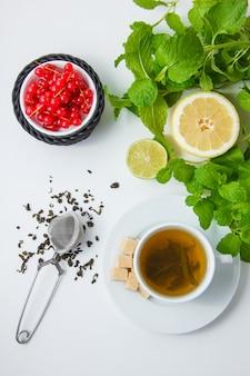 Vista superior de una taza de té con limón, azúcar, hojas de menta, frambuesa sobre superficie blanca. vertical
