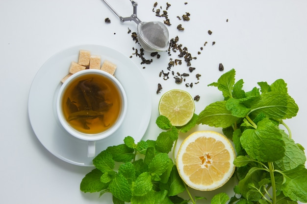 Vista superior de una taza de té con limón, azúcar, hojas de menta en la superficie blanca. horizontal