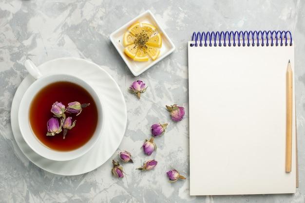 Vista superior de la taza de té con limón y bloc de notas en el escritorio blanco