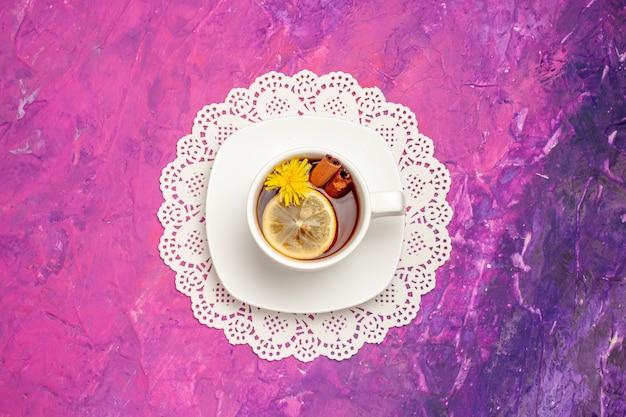 Vista superior de la taza de té con limón y canela en el caramelo de color rosa té de mesa