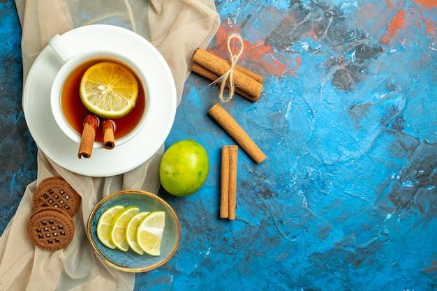Vista superior de la taza de té con limón y canela, galletas de mantón beige limón en el lugar de copia de la superficie roja azul