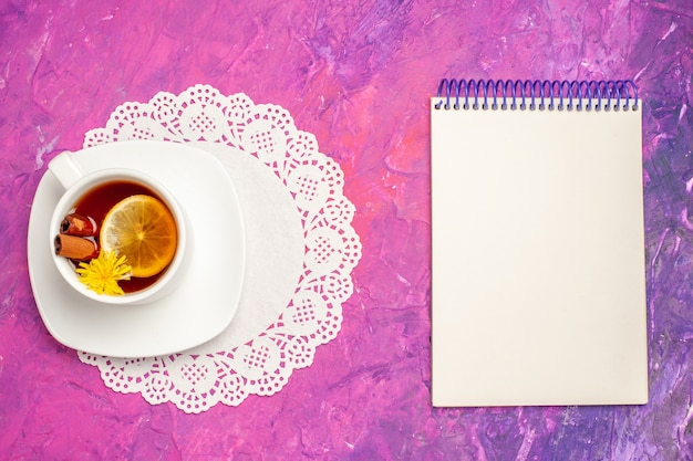 Vista superior de la taza de té con limón y canela en la mesa rosa té color caramelo