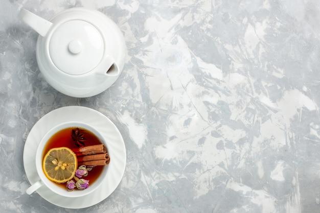 Vista superior de una taza de té con limón y canela sobre la superficie blanca clara