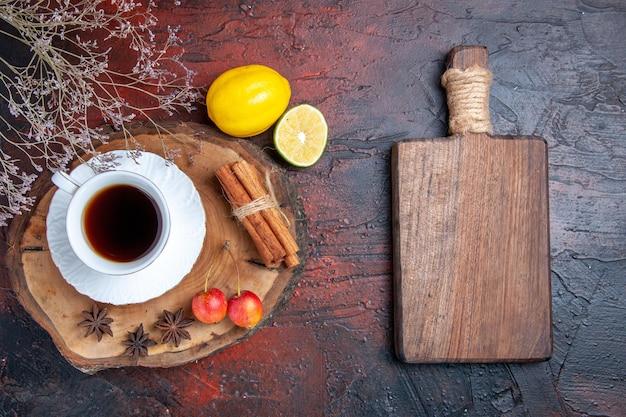 Vista superior de una taza de té con limón y canela sobre una superficie oscura