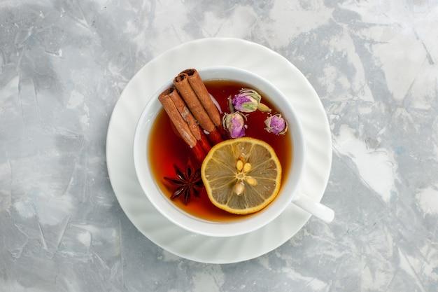 Vista superior de una taza de té con limón y canela en la superficie blanca