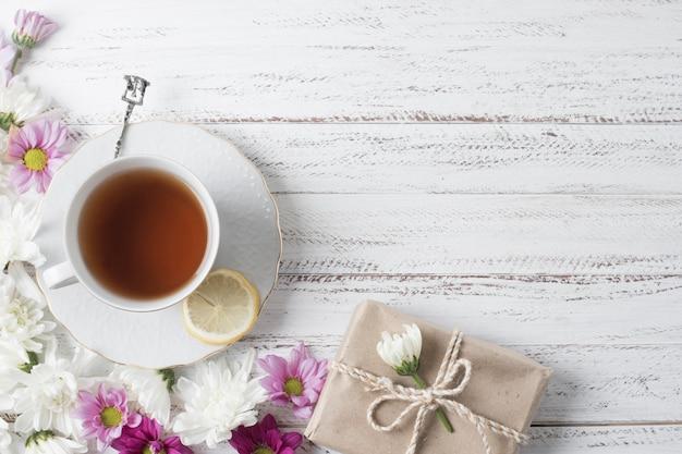 Vista superior de la taza de té de limón decorada con flores y caja de regalo en el escritorio de madera