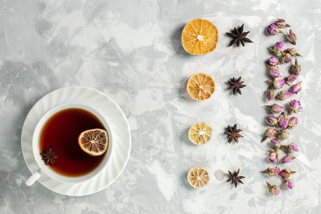 Vista superior de la taza de té con limón y flores en el escritorio de color blanco claro