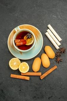 Vista superior de una taza de té con limón y galletas en el escritorio oscuro