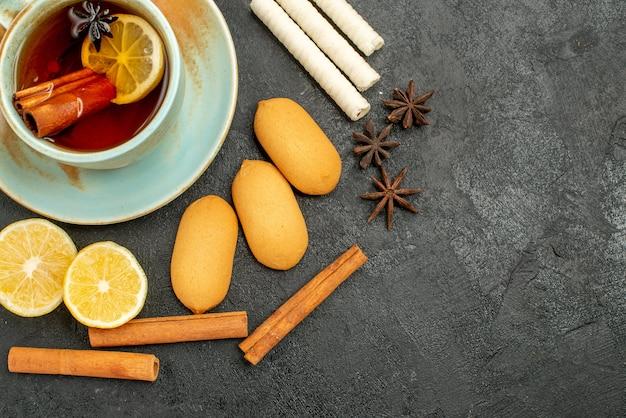 Vista superior de una taza de té con limón y galletas en el fondo oscuro