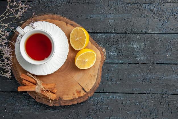 Vista superior de una taza de té con limón en la mesa oscura