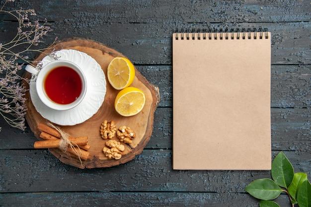 Vista superior de una taza de té con limón y nueces en la mesa oscura