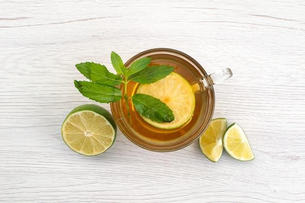 Vista superior de una taza de té con limón verde y min en blanco, agua de té de frutas