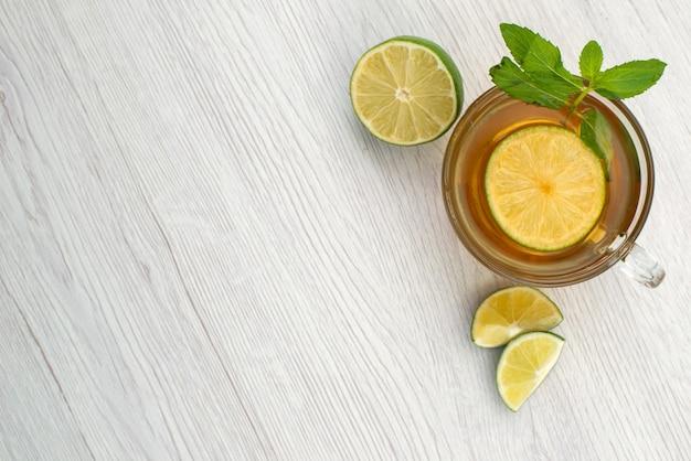 Vista superior de una taza de té con limón verde sobre blanco, fruta de bebida líquida