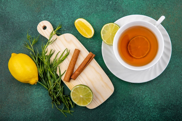 Vista superior de una taza de té con limones y ramas de canela en la placa de cocina de madera en gre