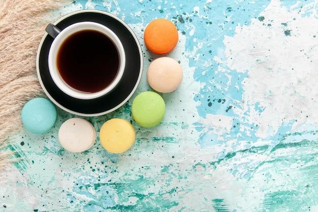 Vista superior de la taza de té con macarons franceses en el escritorio azul