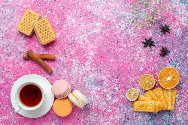 Vista superior de la taza de té con macarons franceses y galletas en el escritorio rosa claro