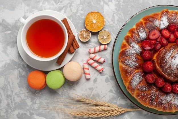 Vista superior de una taza de té con macarons franceses y tarta de fresa sobre una superficie blanca clara