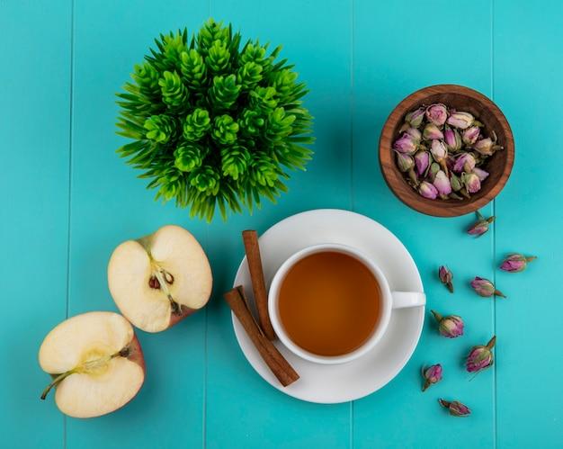 Vista superior taza de té con manzana verde canela y capullos de rosa secos sobre un fondo azul.