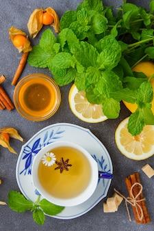 Vista superior de una taza de té de manzanilla con hojas de menta, limón, miel, canela seca.