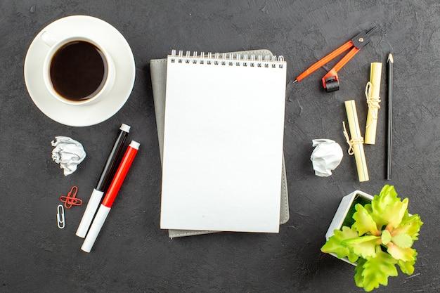 Vista superior de la taza de té, marcadores rojos y negros, clips de carpeta, brújulas, cuaderno sobre mesa negra