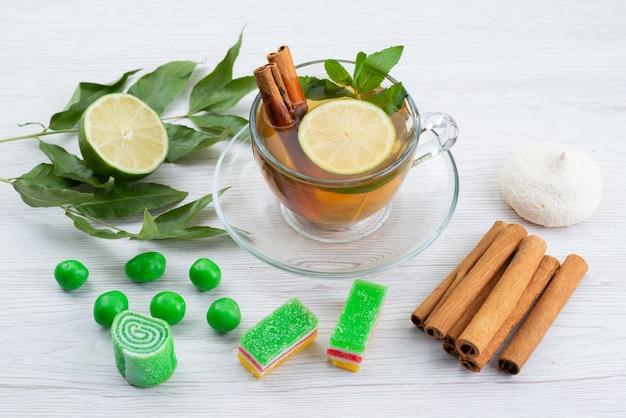 Vista superior de una taza de té con mermelada de limón y menta y canela sobre blanco, dulces de postre de té