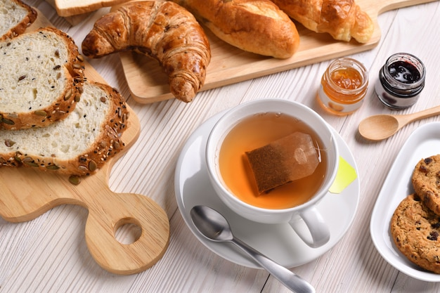 Vista superior de la taza de té con pan o bollo, croissant y panadería en mesa de madera blanca