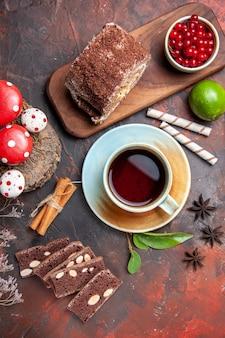 Vista superior de la taza de té con pastel y rollo de galletas sobre una superficie oscura
