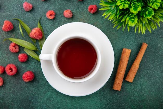 Vista superior de la taza de té en el platillo y canela con frambuesas y hojas en verde