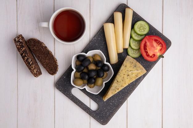 Vista superior taza de té con quesos ahumados con aceitunas tomate pepino y rebanadas de pan negro sobre fondo blanco.