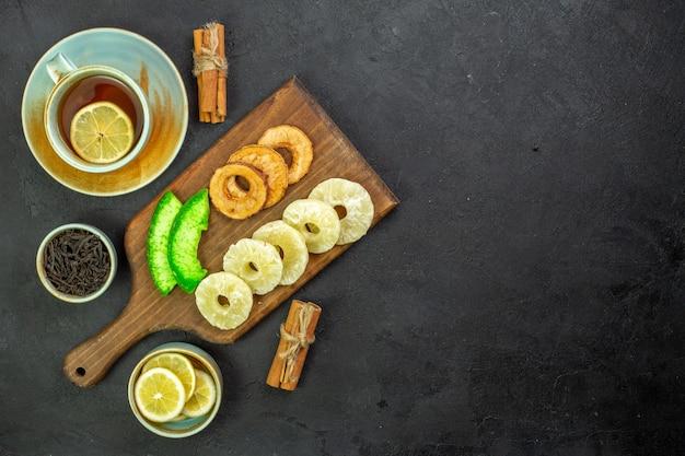 Vista superior de una taza de té con rodajas de limón y frutos secos