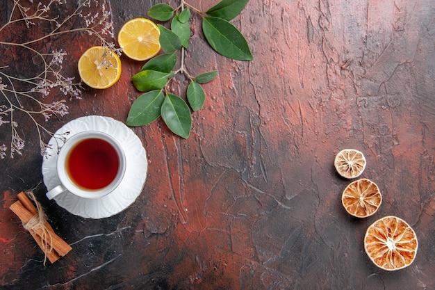 Vista superior de la taza de té con rodajas de limón en la mesa oscura azúcar té foto galleta dulce