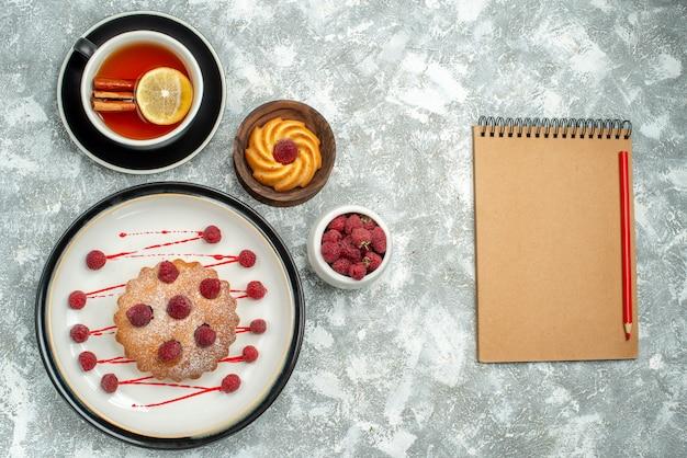 Vista superior de una taza de té con rodajas de limón y pastel de bayas de canela en un cuaderno de placa ovalada en superficie gris