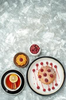 Vista superior de una taza de té con rodajas de limón y pastel de bayas de canela en un plato ovalado en el lugar de copia de superficie gris