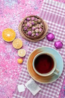 Vista superior de la taza de té con rodajas de naranja y caramelos en la superficie rosa