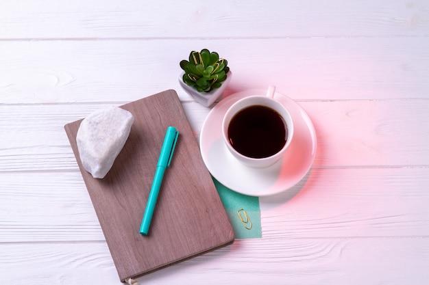Vista superior de una taza de té con rotulador y planta. fondo de escritorio blanco.