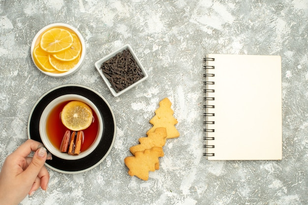 Vista superior de una taza de té en un tazón de galletas de mano de mujer con cuaderno de rodajas de chocolate y limón sobre superficie gris