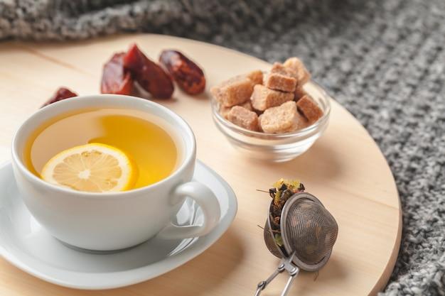 Vista superior de una taza de té con trozo de limón en la mesa de madera