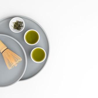 Vista superior de tazas con té matcha y batidor de bambú