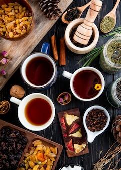 Vista superior de tazas de té y varias especias y hierbas con frutos secos y frutas secas en rústico
