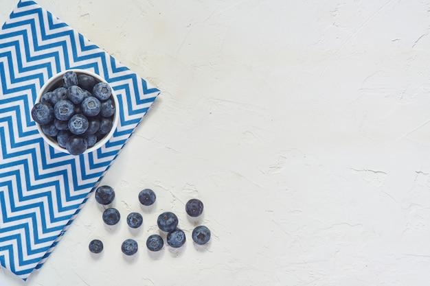 Vista superior del tazón con arándanos en azul textilr y hormigón blanco