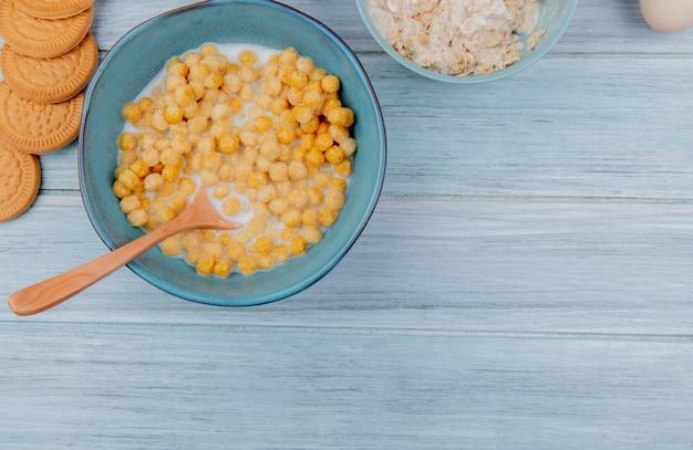 Vista superior del tazón de cereales para el desayuno y la leche con galletas de cuchara de madera copos de avena sobre fondo de madera